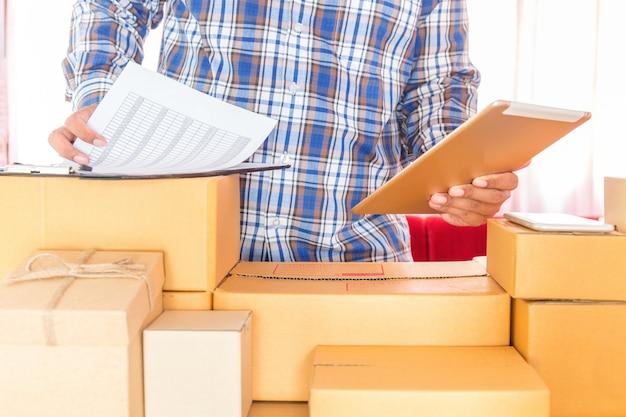 Geschäftsmann, der mit handy arbeitet und zu hause büro des braunen paketkastens verpackt. händeverkäufer bereiten das produkt vor, das bereit ist, zum kunden zu liefern. online-verkauf, e-commerce starten sie versand-konzept.