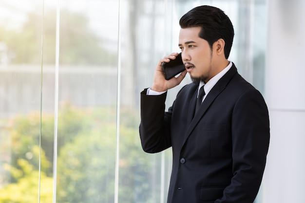 Geschäftsmann, der mit handy im büro spricht