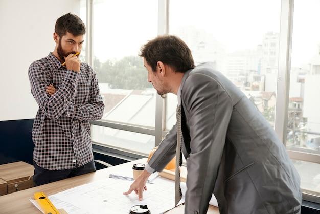 Geschäftsmann, der mit ingenieur im büro arbeitet