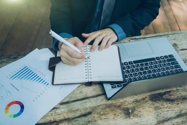 Geschäftsmann, der mit intelligentem telefon, tablette, notizbuch und laptop auf hölzernem schreibtisch arbeitet.