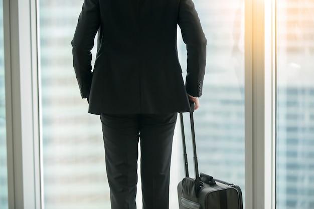 Geschäftsmann, der mit koffer nahe dem fenster steht