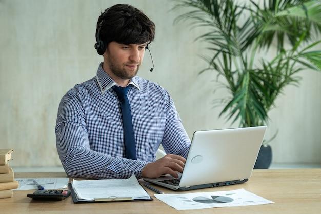 Geschäftsmann, der mit kollegenteam im videoanrufkonferenzmann spricht, der laptop und kopfhörer für online-besprechung verwendet