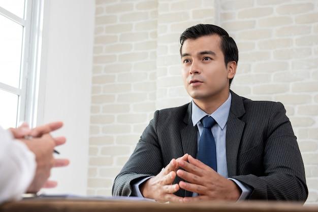 Geschäftsmann, der mit kunden am tisch verhandelt, bevor er eine vereinbarung trifft