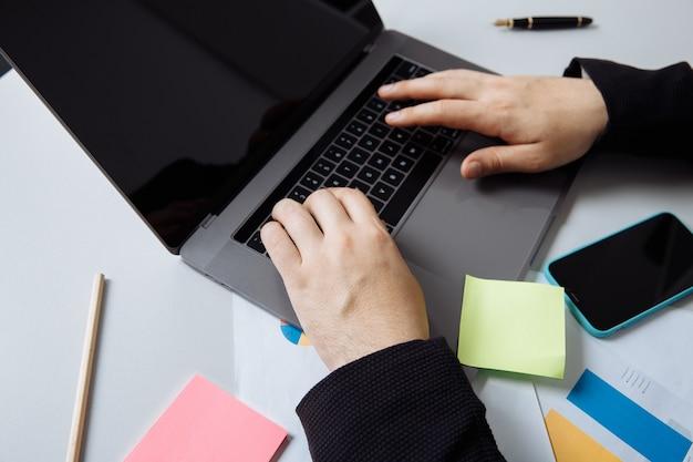 Geschäftsmann, der mit laptop am schreibtisch arbeitet.