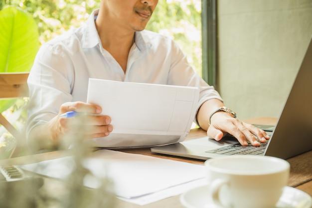 Geschäftsmann, der mit laptop arbeitet und papierkram und dokumente im büro hält.
