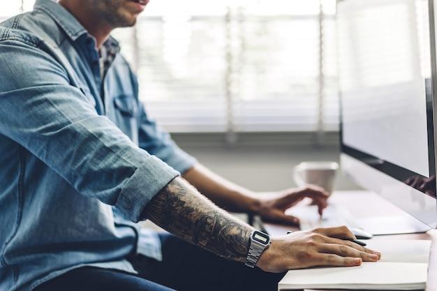 Geschäftsmann, der mit laptop-computer arbeitet. kreative geschäftsleute, die stift in modernem arbeitsloft planen und verwenden