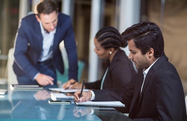 Geschäftsmann, der mit mitarbeitern in einer besprechung im konferenzraum interagiert