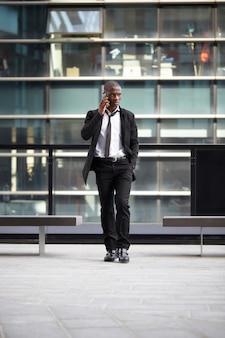 Geschäftsmann, der mit mobile und laptop in der städtischen umwelt arbeitet