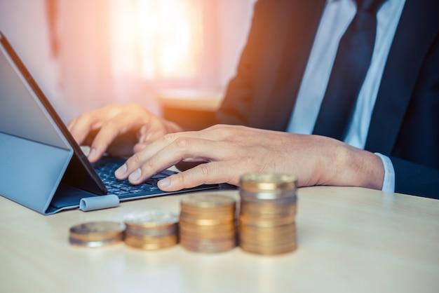 Geschäftsmann, der mit münzgeldwährung arbeitet. konzept des investitionswachstums und der geldersparnis.