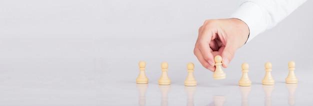 Geschäftsmann, der mit schachspiel im wettbewerbserfolgsspiel, in der konzeptgeschäftsarbeitgeberstrategie und im erfolgreichen management oder in der führung platziert