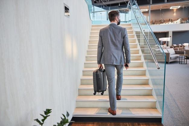 Geschäftsmann, der mit seinem handgepäck die treppe hinaufsteigt