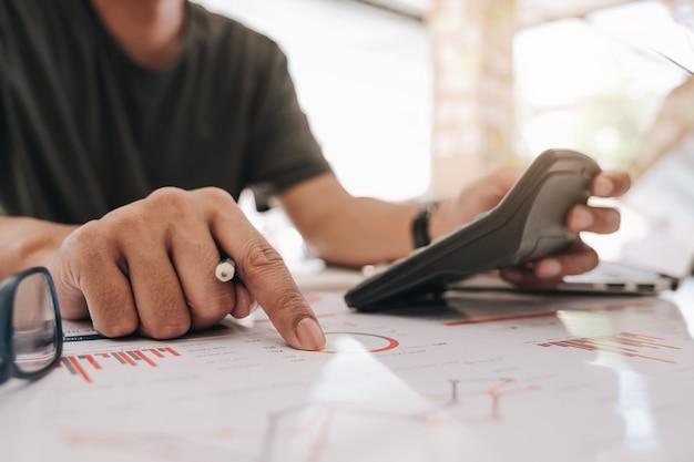 Geschäftsmann, der mit taschenrechner für finanzdokument im büro arbeitet. männlicher buchhalter, der buchhaltung und berechnung erledigt. buchhalter, der berechnung bildet. ersparnisse, finanzen
