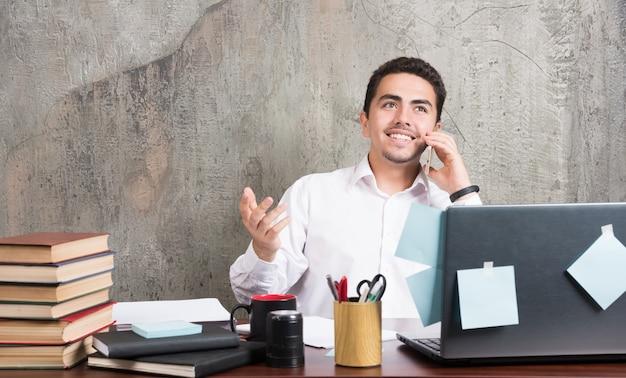 Geschäftsmann, der mit telefon glücklich am schreibtisch spricht.