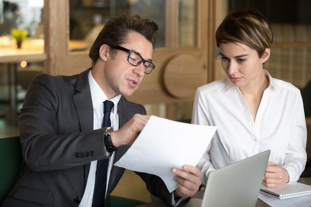 Geschäftsmann, der mit weiblichem kollegen über vertragsbedingungen sich berät