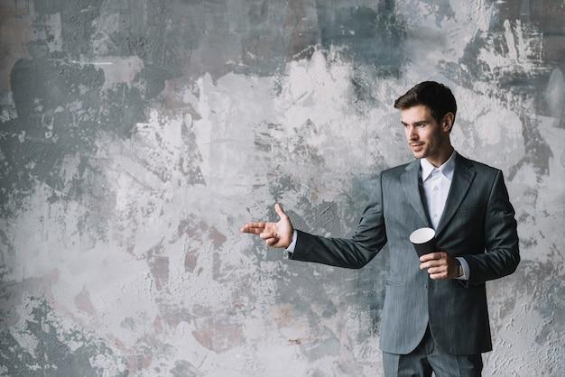 Geschäftsmann, der mitnehmerkaffeetasse macht handgewehrgeste gegen schmutzwand macht