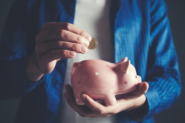 Geschäftsmann, der münze in das sparschwein einsetzt