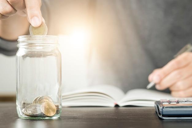 Geschäftsmann, der münze in glasglas und in aufzeichnung auf notizbuch setzt. das spart und investiert
