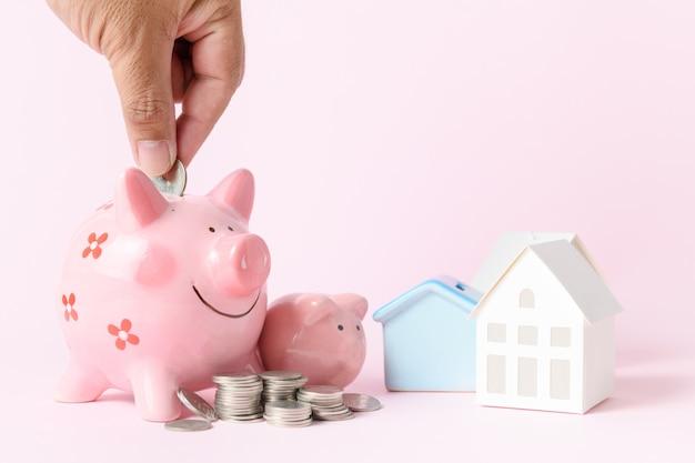 Geschäftsmann, der münze zum sparschwein, rosa hintergrund setzt