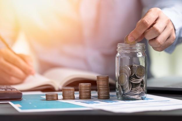 Geschäftsmann, der münze zum speichern des glases setzt und in notizbuch schreibt. geld sparen für das finanzkonzept des investitionskonzepts.