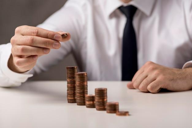 Geschäftsmann, der münze zum stapel hinzufügt