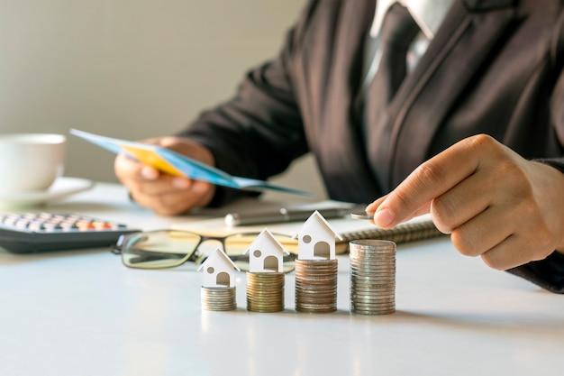 Geschäftsmann, der münzen auf einen haufen münzen mit finanzkonzept-hausmodell setzt
