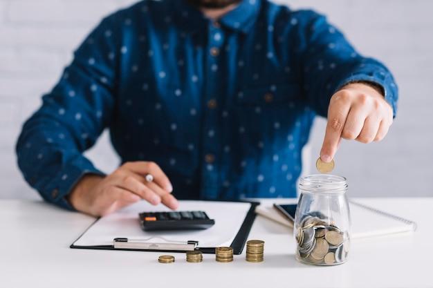 Geschäftsmann, der münzen in glas unter verwendung des taschenrechners am arbeitsplatz einsetzt