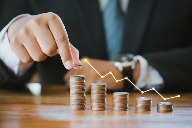 Geschäftsmann, der münzen mit einer grafik des gewinns stapelt. finanzsparkonzept