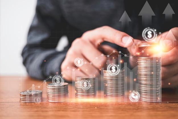 Geschäftsmann, der münzen stapelt, die mit virtueller grafik und währungszeichen wie dollar pfund sterling yen yuan und euro stapeln. konzept für unternehmensinvestitionen und gewinneinsparungen.