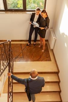 Geschäftsmann, der nach oben treffen mit geschäftsfrauen geht. geschäftsführende kollegen auf treppen im firmengebäude. partnerschaftliche teamarbeit. professionelles gespräch am geschäftigen arbeitsplatz.