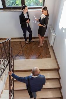 Geschäftsmann, der nach oben treffen mit geschäftsfrauen geht. geschäftsleiterkollegen auf treppen im firmengebäude