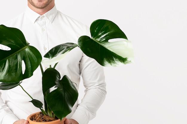 Geschäftsmann, der nachhaltige geschäftslösung mit vergossenem plan hält