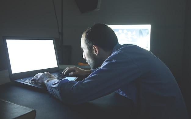 Geschäftsmann, der nachts einen laptop an seinem schreibtisch benutzt.