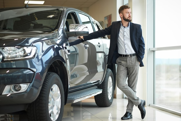 Geschäftsmann, der nahen jeep in der automitte steht.