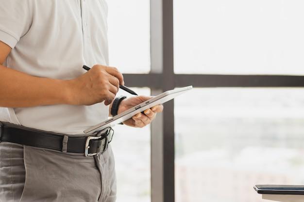Geschäftsmann, der neben dem fenster in seinem büro steht und ein digitales tablet hält Premium Fotos