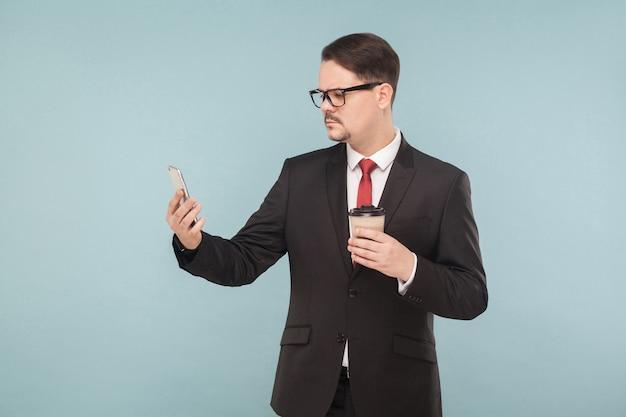 Geschäftsmann, der neue telefon- und gesichts-id testet. zukunftstechnologien. indoor, studioaufnahme, isoliert auf hellblauem oder grauem hintergrund