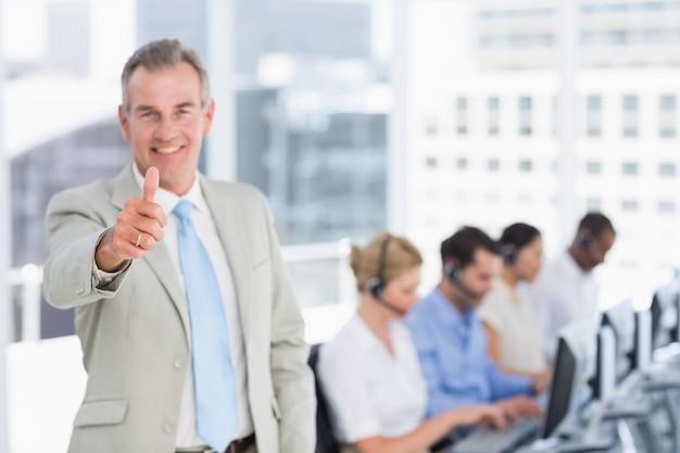 Geschäftsmann, der oben daumen mit den führungskräften gestikuliert, die computer verwenden