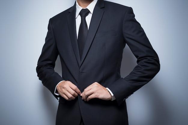 Geschäftsmann, der oben einen schwarzen anzug ankleidet