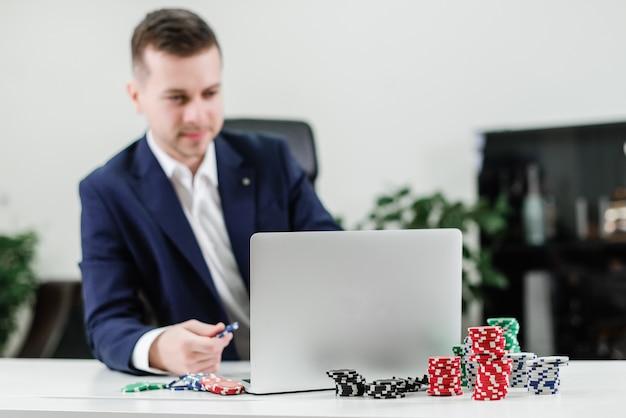Geschäftsmann, der on-line-kasino und schürhaken über laptop spielt