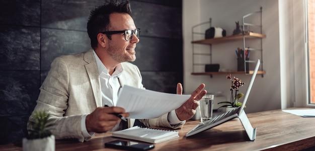 Geschäftsmann, der on-line-sitzung in seinem büro hat