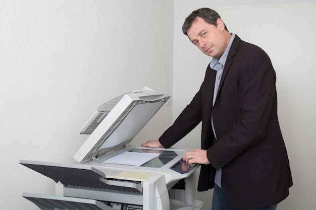 Geschäftsmann, der papier auf fotokopiergerät im büro hält