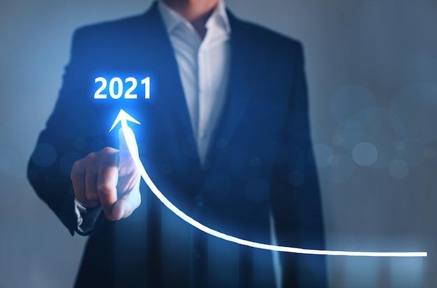 Geschäftsmann, der pfeilgraph zeigt, zukünftiges wachstumsjahr 2021. entwicklung zum erfolg und wachsendes wachstumskonzept.
