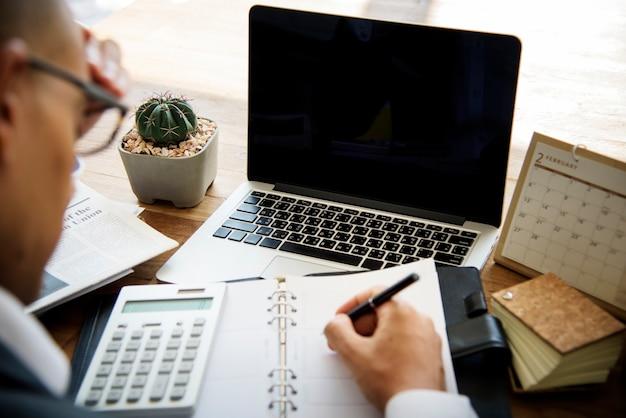 Geschäftsmann, der planungs-berechnungs-schreiben auf einem holztisch arbeitet