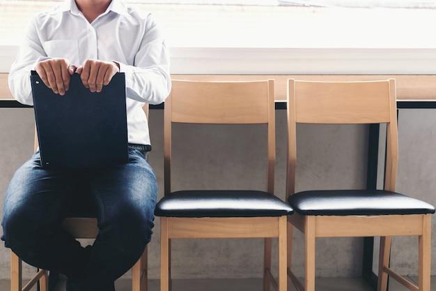 Geschäftsmann, der portefeuillebericht beim sitzen auf stuhl hält