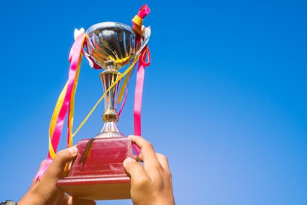 Geschäftsmann, der preistrophäengold mit bandshowsieg für beste erfolgsleistung und preis des geschäfts als siegerwettbewerb mit blauem himmel hält