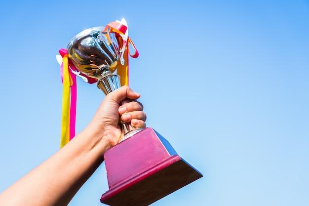 Geschäftsmann, der preistrophäengold mit bandshowsieg für besten erfolgsleistungspreis des geschäfts hält