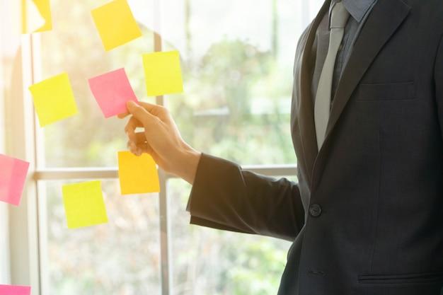 Geschäftsmann, der projektplan und aufgabe im beweglichen prozess für team darstellt