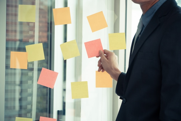 Geschäftsmann, der projektplan und aufgabe im beweglichen prozess für team im konferenzzimmer darstellt