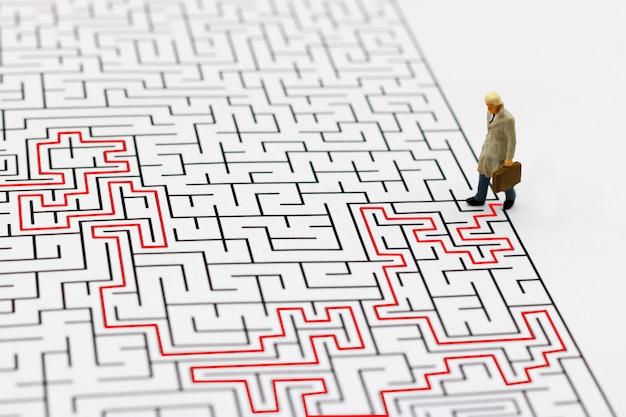 Geschäftsmann, der punkt des labyrinths beginnen geht.