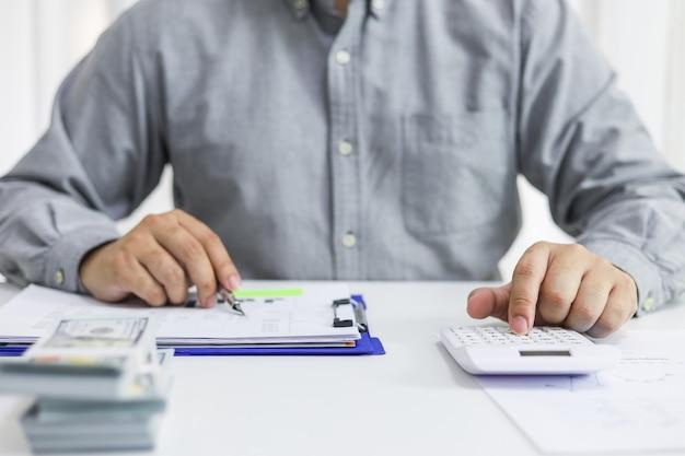 Geschäftsmann, der rechnungen prüft. steuern bankkontostand und berechnung des jahresabschlusses