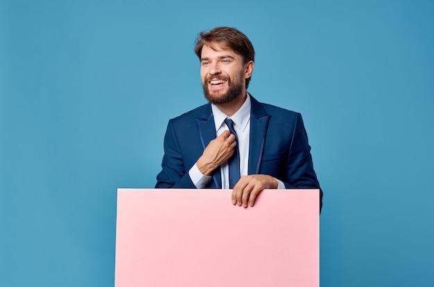 Geschäftsmann, der rosa werbetafel auf blauem hintergrund hält.